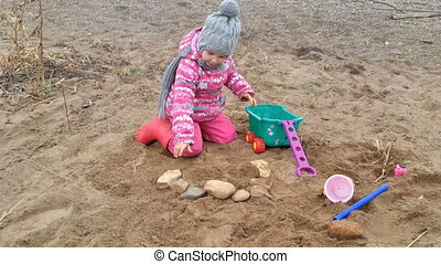 little girl plays on coast stones