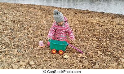 little girl plays on coast stones