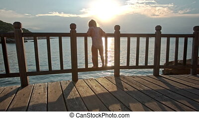 Little Girl Plays on Floor in Beach Cafe at Sunset Backlight