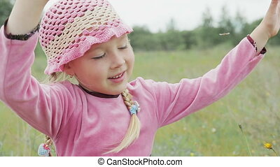 little girl plays on the field - little girl in a pink hat,...