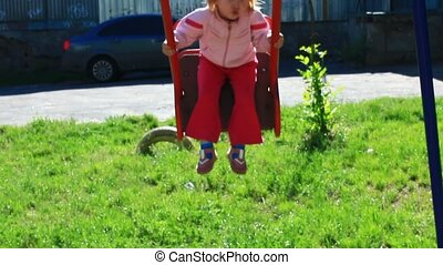 little girl plays on the swing