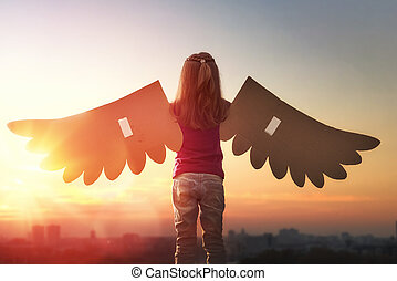 Kid with the wings of a bird - Little girl plays outdoors. ...