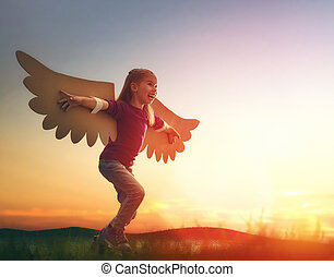 Kid with the wings of a bird - Little girl plays outdoors....