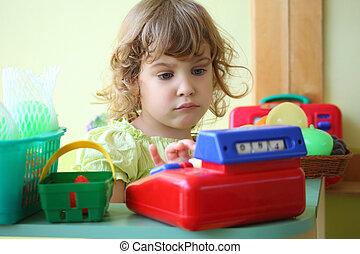 little girl plays shop