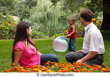 Little girl plays with big inflatable ball in park in afternoon. Parents observe of it sitting on lawn.