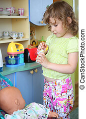 little girl plays with doll on kitchen