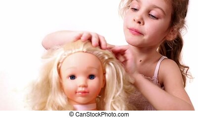 Little girl plays with dolls hairdo, isolated