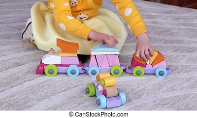 Little girl plays with educational toy train, sitting on a...