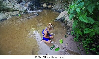 Little Girl Plays with Leaves in Pond Shallow Water