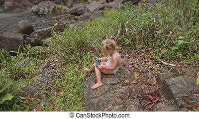 Little Girl Plays with Phone on Stone against Waterfall