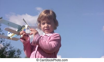 Little girl plays with toy plane.