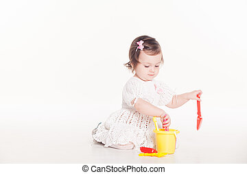 little girl plays with toys on a white background