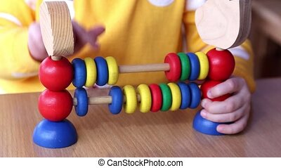 Little girl plays with wooden colored educational toy...