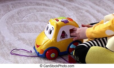 Little girl plays with yellow educational toy car, sitting...