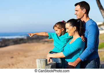 little girl pointing at ocean with parents - adorable little...
