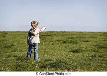 little girl pointing something in the horizont