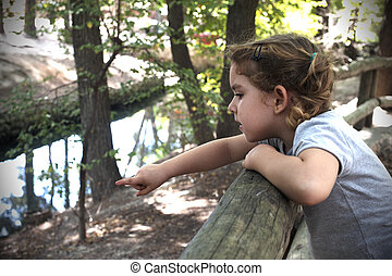 little girl pointing the finger and looking into a river