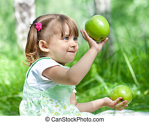 Little girl portrait with 2 green apples in her hands outdoor