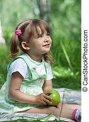 Little girl portrait with green apple in her hands outdoor