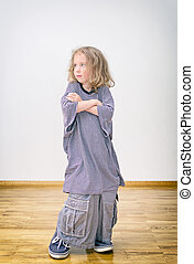 Little girl posing in oversized shorts and shirt.