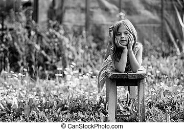Little girl posing in the yard of a country house. Black and white photo.