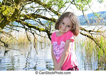 Little girl posing on a lake
