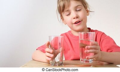 little girl pouring water from one glass to another