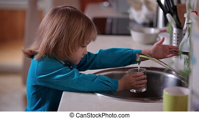 Little girl pours in a glass of water