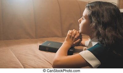 Little girl praying in the night. Little girl hand praying. little girl holy bible prays with bible lifestyle in her hands. the catholicism sacred holy bible. children and religion upbringing faith symbol. Little girl with praying. Peace, hope , dreams concept