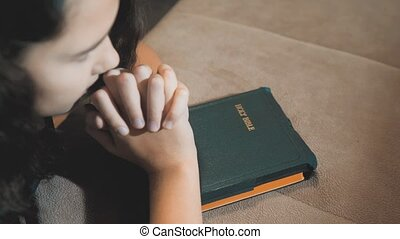 Little girl praying in the night. Little girl hand praying. little girl holy bible prays with bible in her hands. the catholicism sacred holy bible . children and religion upbringing faith symbol . Little girl with praying lifestyle . Peace, hope , dreams concept