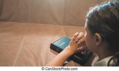 Little girl praying in the night. Little girl lifestyle hand praying. little girl holy bible prays with bible in her hands. the catholicism sacred holy bible. children and religion upbringing faith symbol. Little girl with praying. Peace, hope , dreams concept
