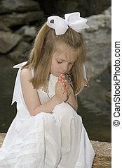 Little girl praying outside