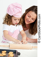 Little girl preparing a dough with her mother in the kitchen