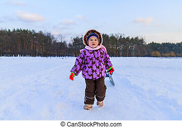 little girl pulls sled in the snow