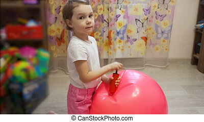 little girl pumps ball in room