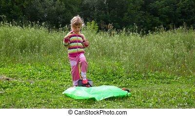 little girl pumps up an inflatable armchair