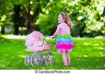 Little girl pushing a toy stroller with doll