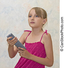 Little girl pushing button on remote controle