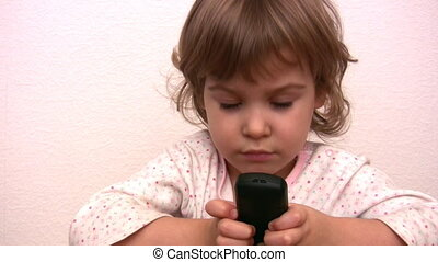 Little girl pushing buttons and talking by phone
