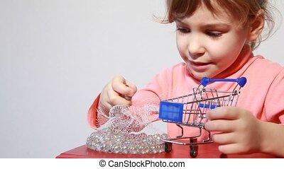 Little girl put white marbles in shopping cart model