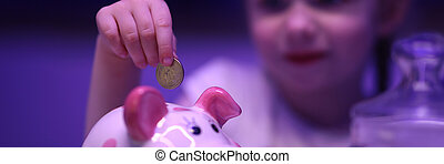Little girl puts coin in piggy bank on table. Teach child ...