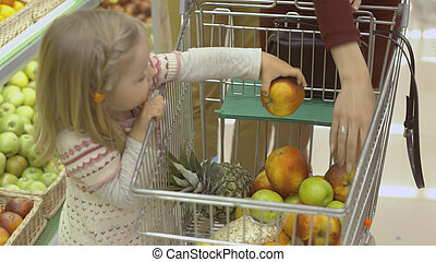 Little girl puts fruits in the trolley