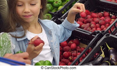 Little girl puts in a grocery basket fresh radish. Family at the grocery store.