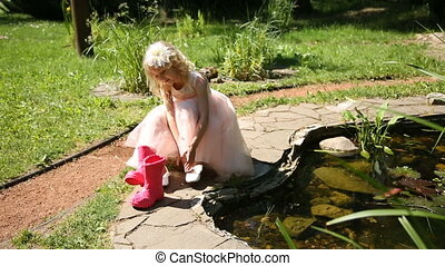 Little girl puts on rubber boots in a flower garden