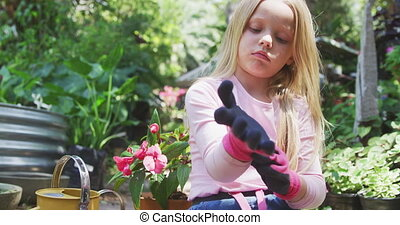 Front view of a Caucasian girl with long blonde hair enjoying time in a sunny garden, putting on her pink gardening gloves in preparation for gardening, in slow motion