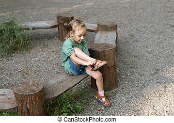Little girl putting her sandal on. She is sitting on a wooden round bench in a summer forest.