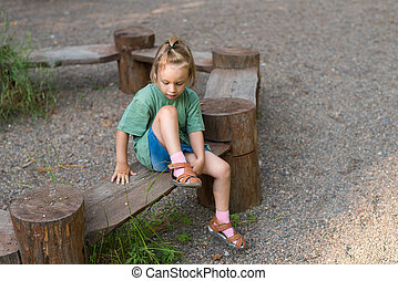 Little girl putting on her sandal