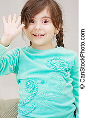 Little girl raises hand in greeting