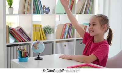 Smiling little girl raising hand to answer at school lesson while sitting in light classroom