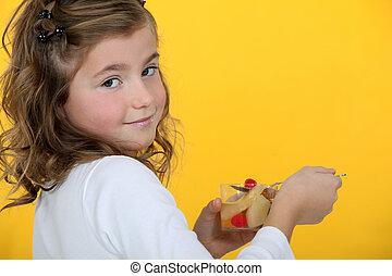 Little girl rating a fruit salad